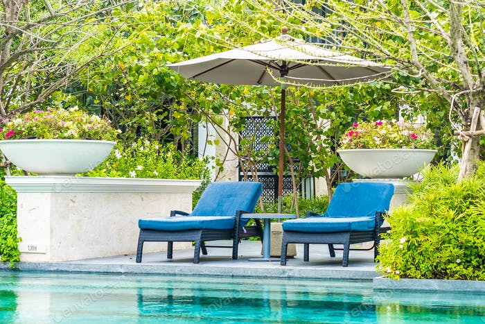 Beautiful outdoor swimming pool in hotel and resort with chair a