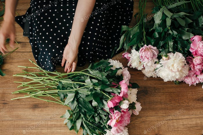 Happy stylish woman arranging peony flowers with cat in room