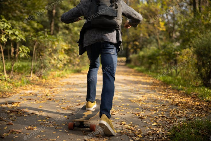 Guy in trendy clothes skateboarding in nature