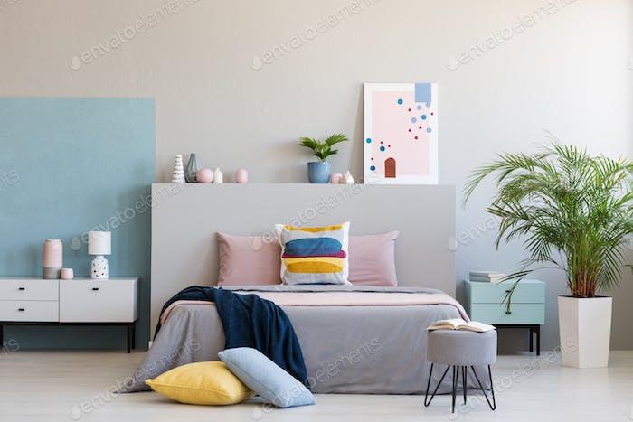 Bunte Kissen auf grauem Bett im modernen Schlafzimmer Interieur mit Pos