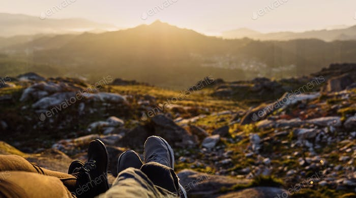 Panoramic detail of two pair of feet in front of a defocused landscape at sunset