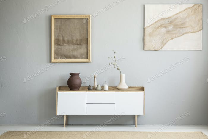 Front view of burlap artworks on a light gray wall above a woode