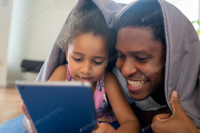 Father and daughter using digital tablet at home.