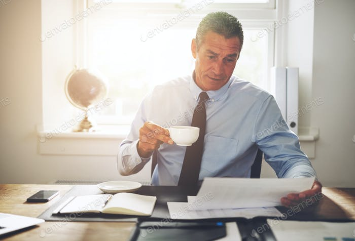 Businessman sitting at his desk drinking coffee and reading documents