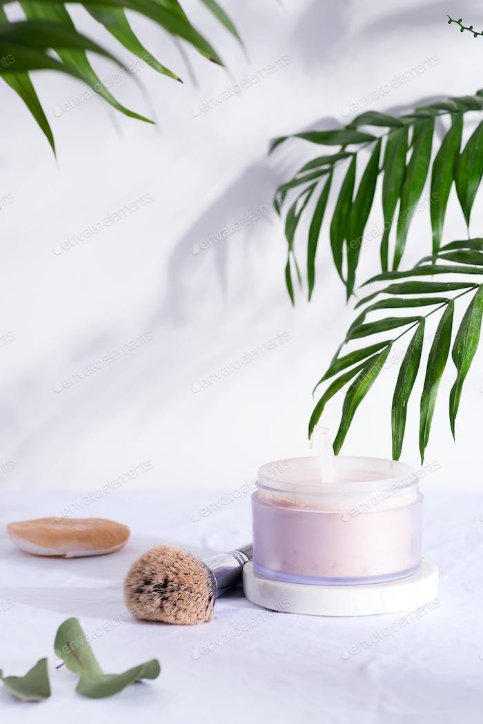 Plastic box with face powder and brush for make-up on a white textile background with green palm