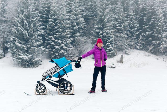 Mutter mit Kinderwagen genießen Mutterschaft im Winterwald
