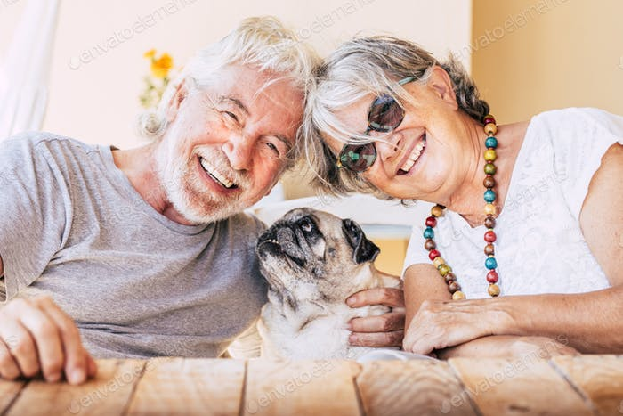 Cheerful old senior couple smile and enjoy her best friend dog pug with love