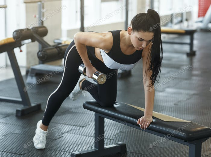 Pretty young woman with dumbbell doing push ups in gym