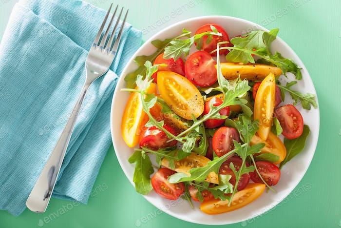 Tomatensalat mit Rucola über grünem Hintergrund