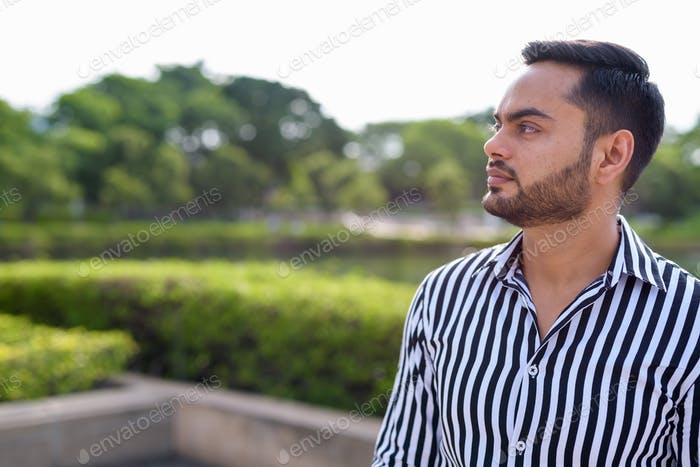 Young bearded Indian businessman relaxing at the park in the cit