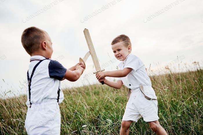 Kämpfe um den Sieg. Zwei Kinder haben Spaß beim Spielen mit Holzschwertern auf dem Feld.