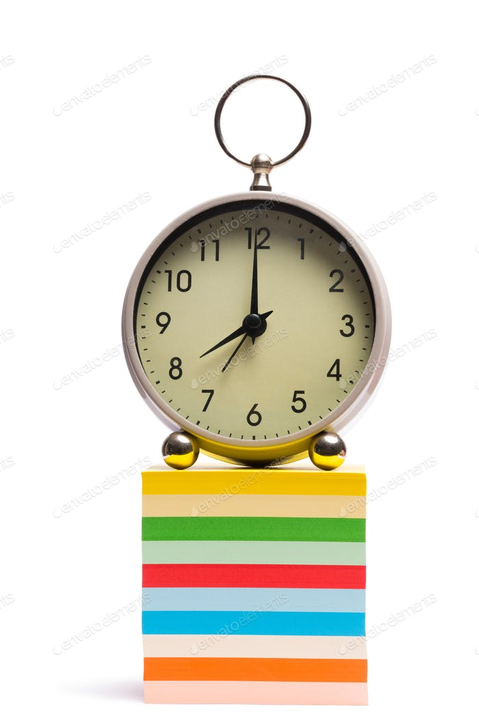 Alarm clock on pile of sticky notes on white background