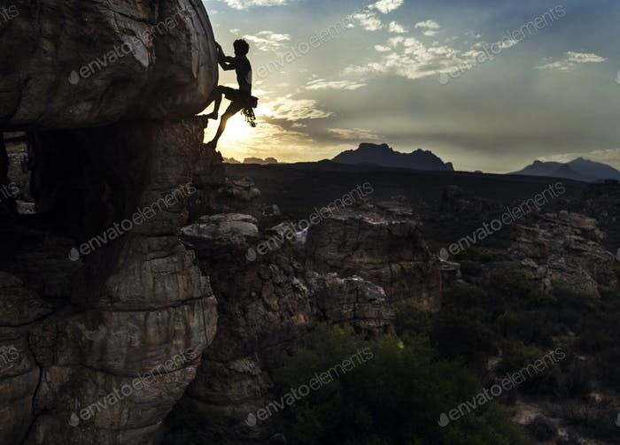 Mountaineer climbing a rock formation in a mountainous landscape.