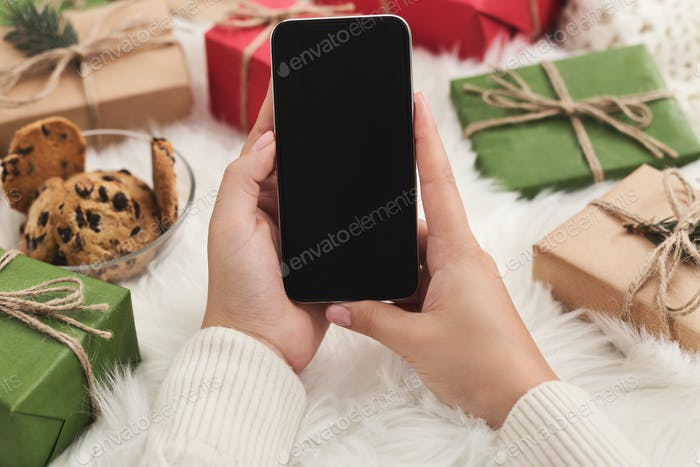 Christmas application. Woman using smartphone mockup, copy space