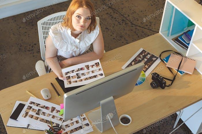 Female graphic designer working at desk in office