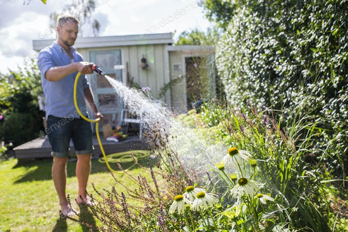 Man watering plants with garden hose