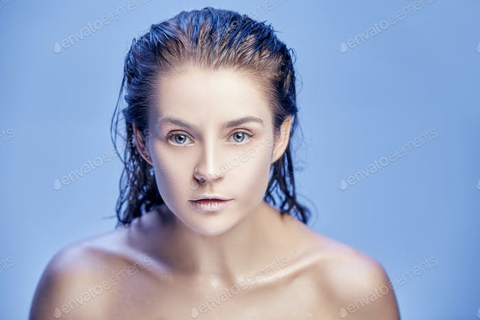Beautiful woman face portrait close up on blue