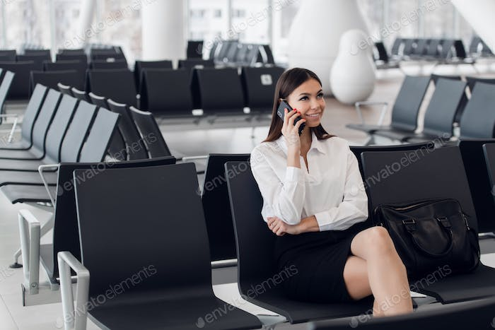 Airport woman on smart phone at gate waiting in terminal. Air travel concept with young casual