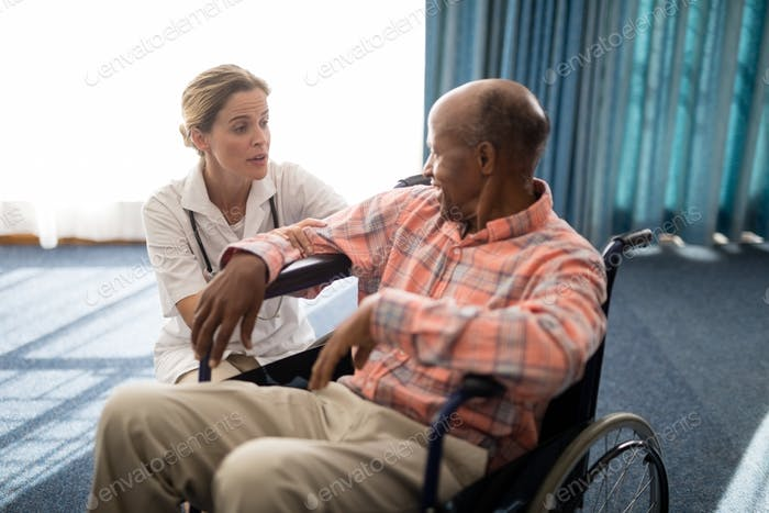 Female doctor kneeling while talking to disabled senior man on wheelchair