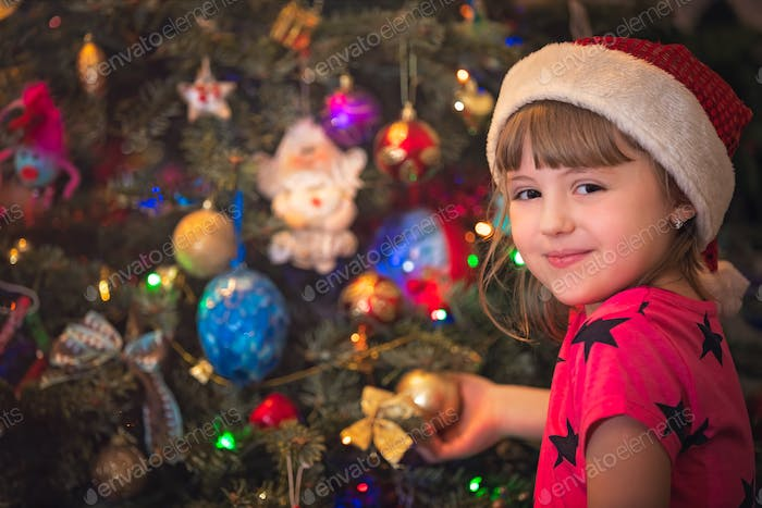 Cute happy girl decorating Christmas tree