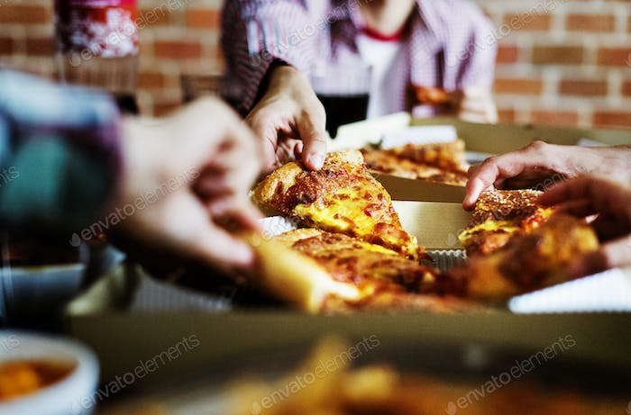 Friends eating pizza together at home