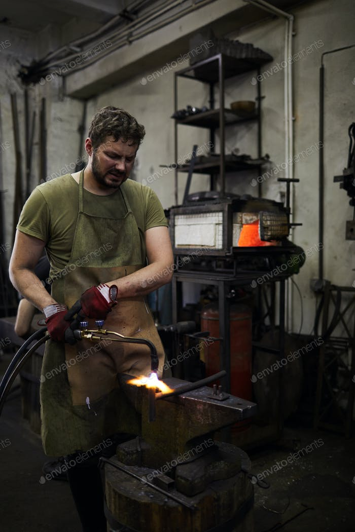 Frowning blacksmith parting metal with cutting torch