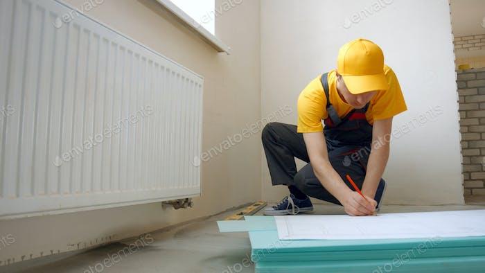 Builder working with blueprint indoors.