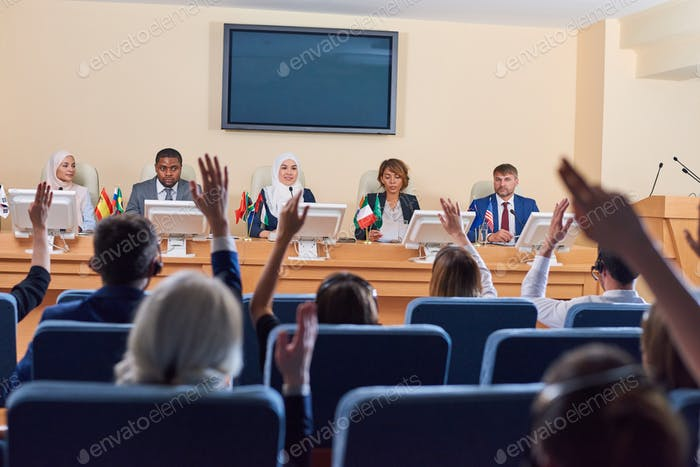 Audience in armchairs raising their hands to ask questions