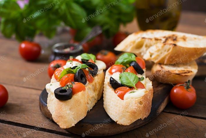 Bruschetta with tomatoes, mozzarella, olives and basil pesto