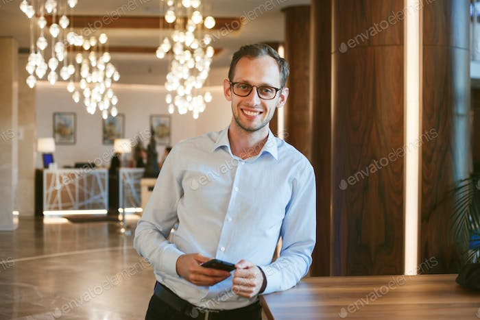 Happy young successful businessman developer keeps phone.