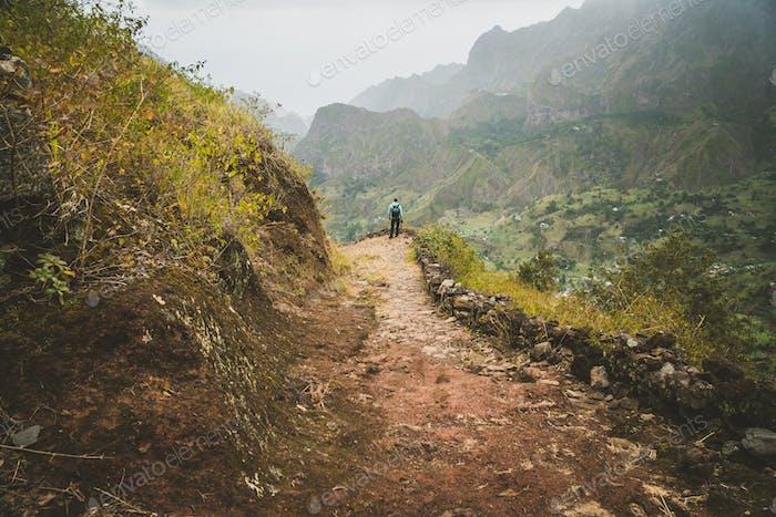 Male hiker enjoying impressive mountainscape. Lash canyon valley extend far below. Santo Antao, Cabo