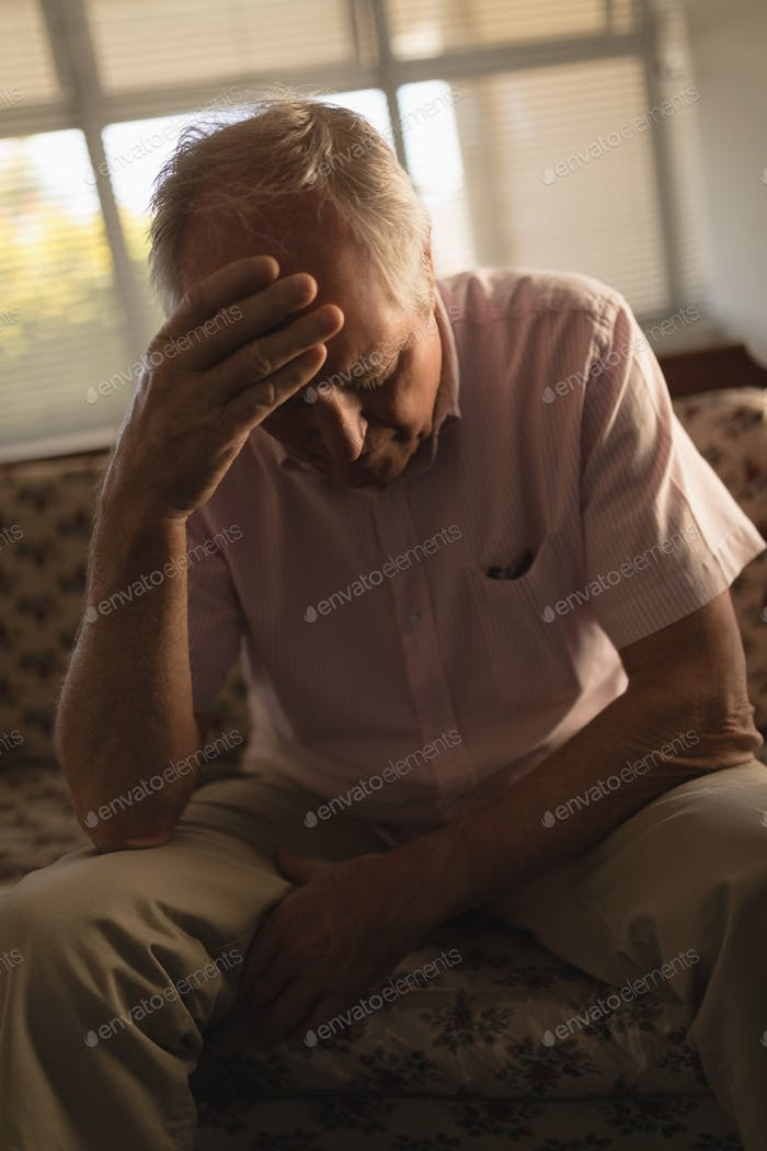 Front view of worried senior man relaxing on sofa in living room at nursing home
