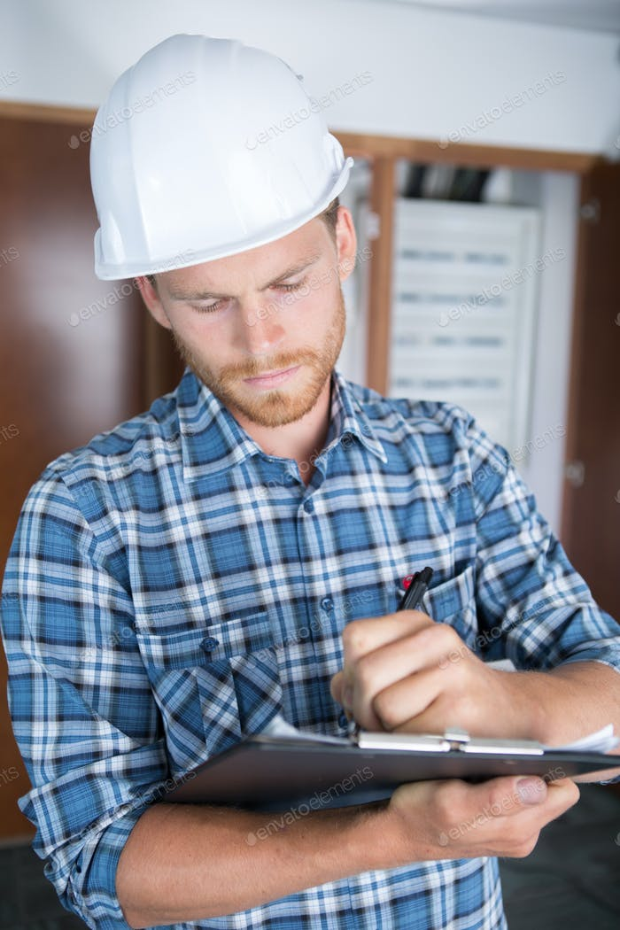 Man in hardhat writing on clipboard