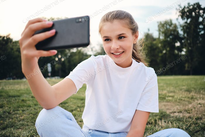 Beautiful smiling girl in white T-shirt happily taking selfie on cellphone sitting on lawn in park