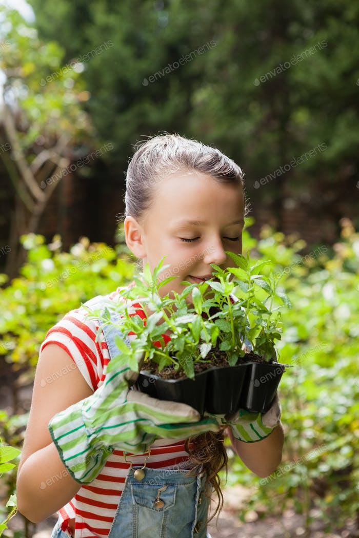 Girl smelling plants with eyes closed