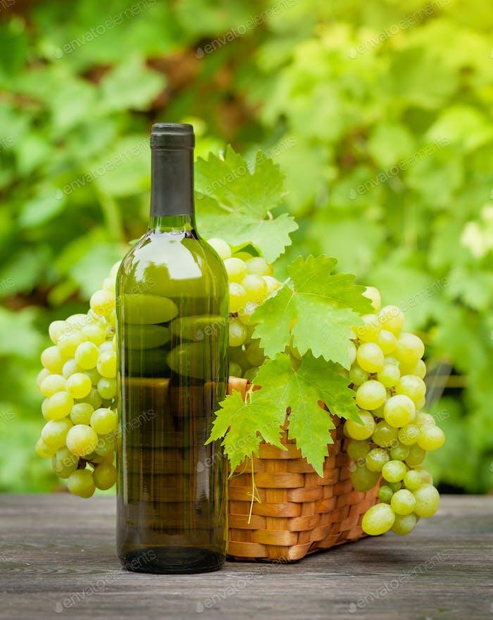 Weißweinflasche und reife Trauben
