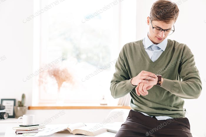 Guy student sit on table looking at watch clock.