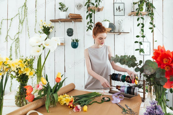Young woman florist making bouquet with flowers and ribbons