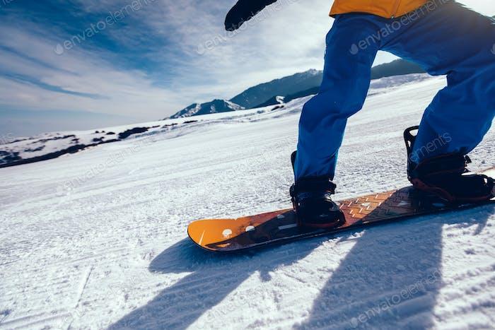 Snowboarder descent on alpine mountain slope