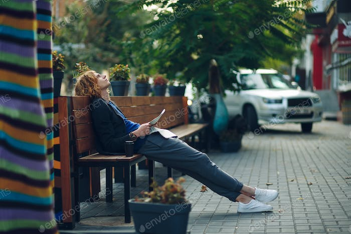 Man dreaming while lying on a long wooden bench