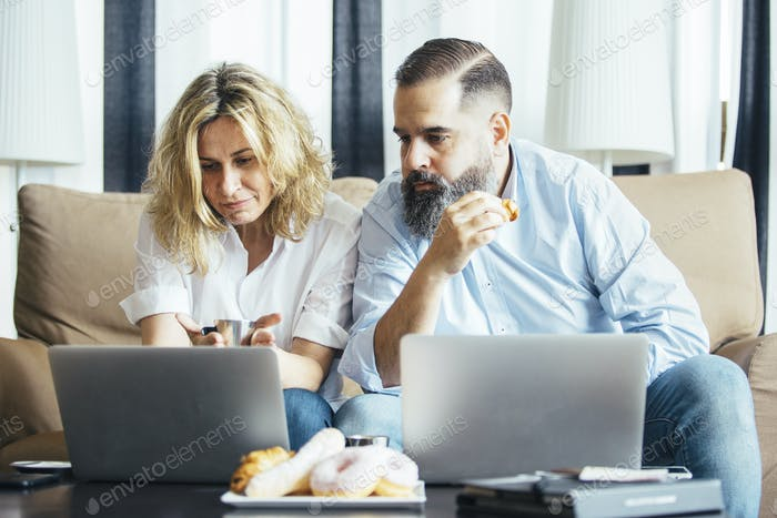 Businesspeople looking at laptop screens