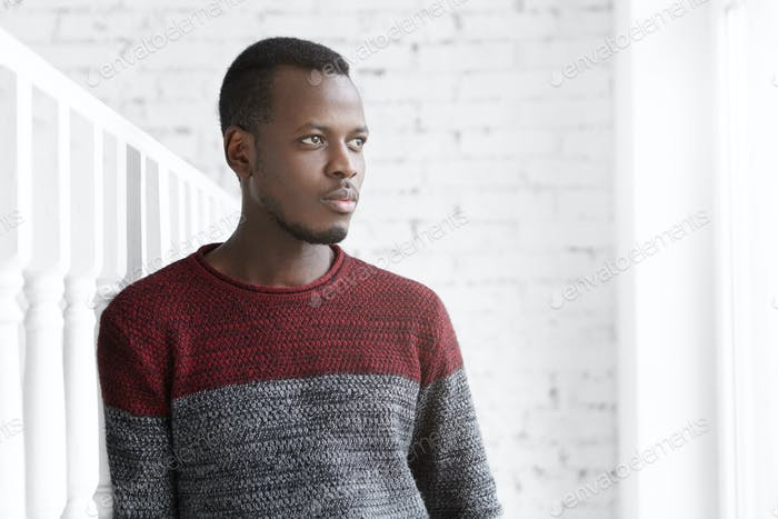 Portrait of thoughtful young Afro-American engineer dressed casually standing in white room, leaning