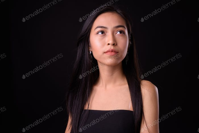 Face of young beautiful Asian woman thinking and looking up