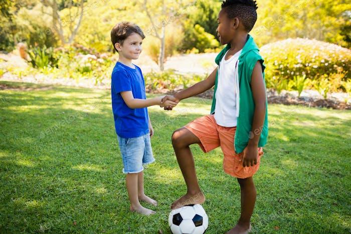 Cute football players handshaking