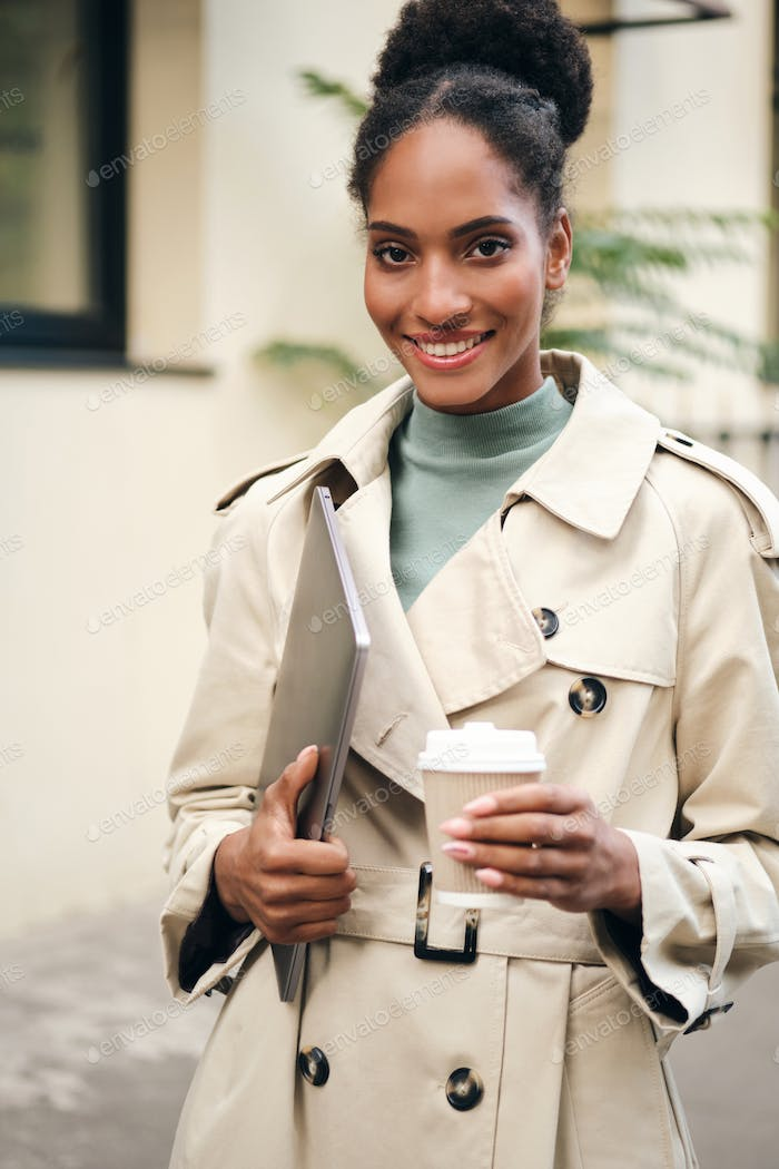 African American business woman in stylish trench coat happily looking in camera on city street