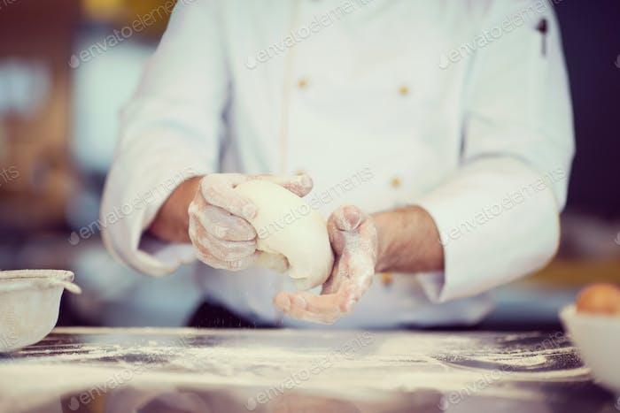 chef hands preparing dough for pizza