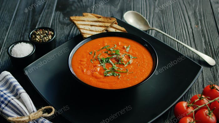 Tomato soup in bowl with crisp bread