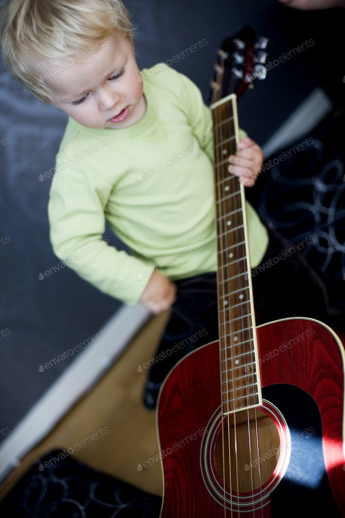 High angle view of boy playing with guitar at home