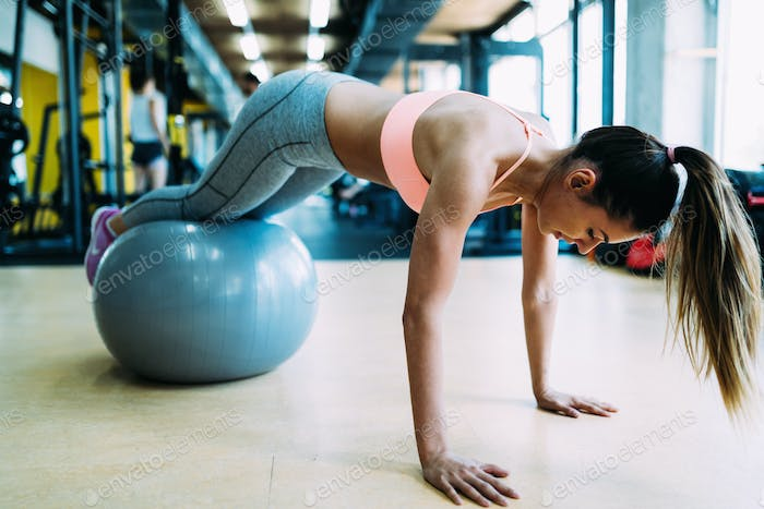 Fitness woman working push ups in gym