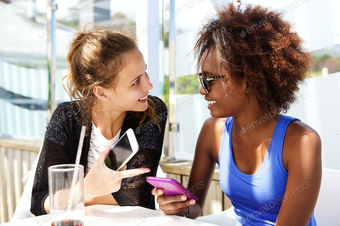 Two friends sitting at restaurant with mobile phone